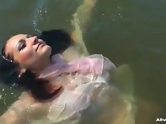 Chick in a sexy blouse takes a dip in the lake