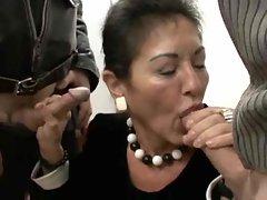 Mature in her work clothes strokes two dicks