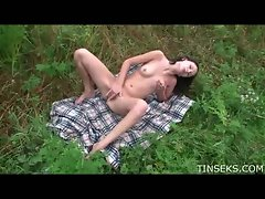 Teen on a blanket in a field masturbating