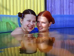 Two teenage girls are playing around in a small swimming pool...